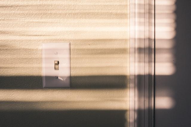 bílý vypínač, béžová zeď.jpg
